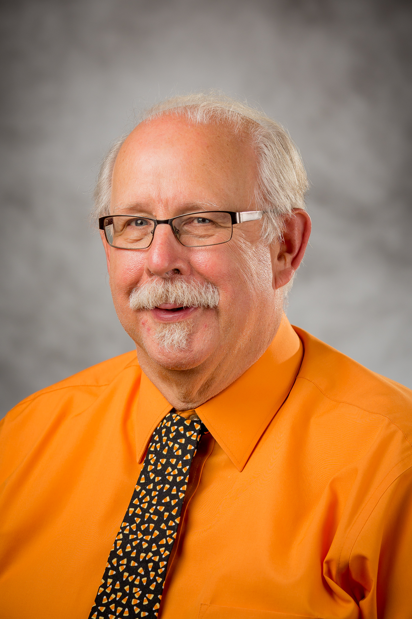 picture of a man with glasses and a orange button up shirt with a candy-corn tie