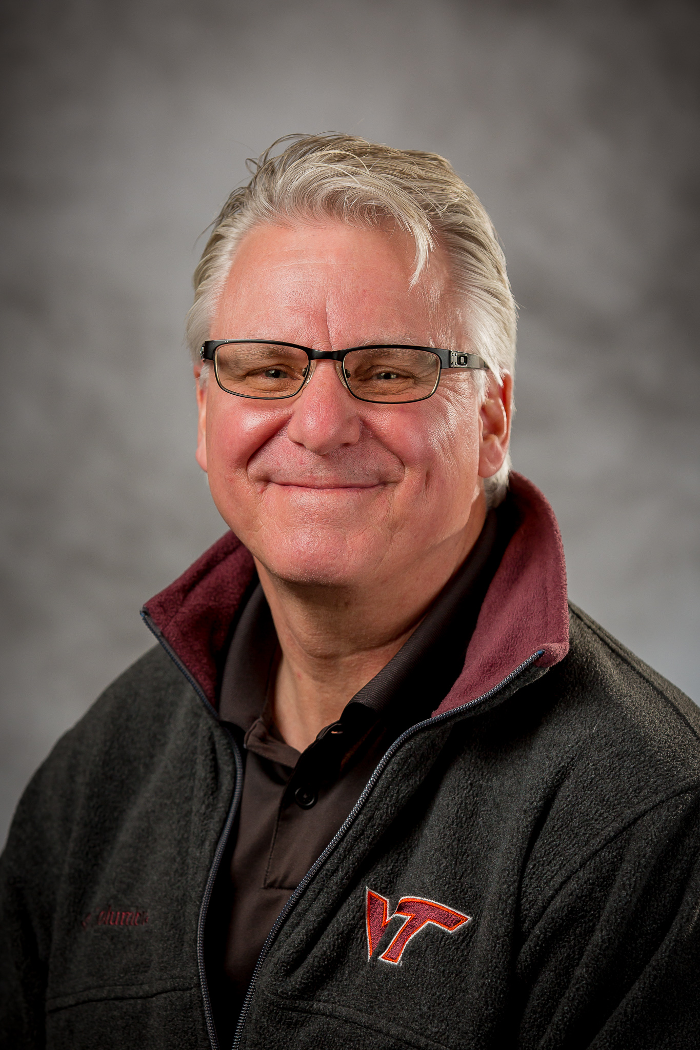 picture of man with glasses wearing a black zip up jacket
