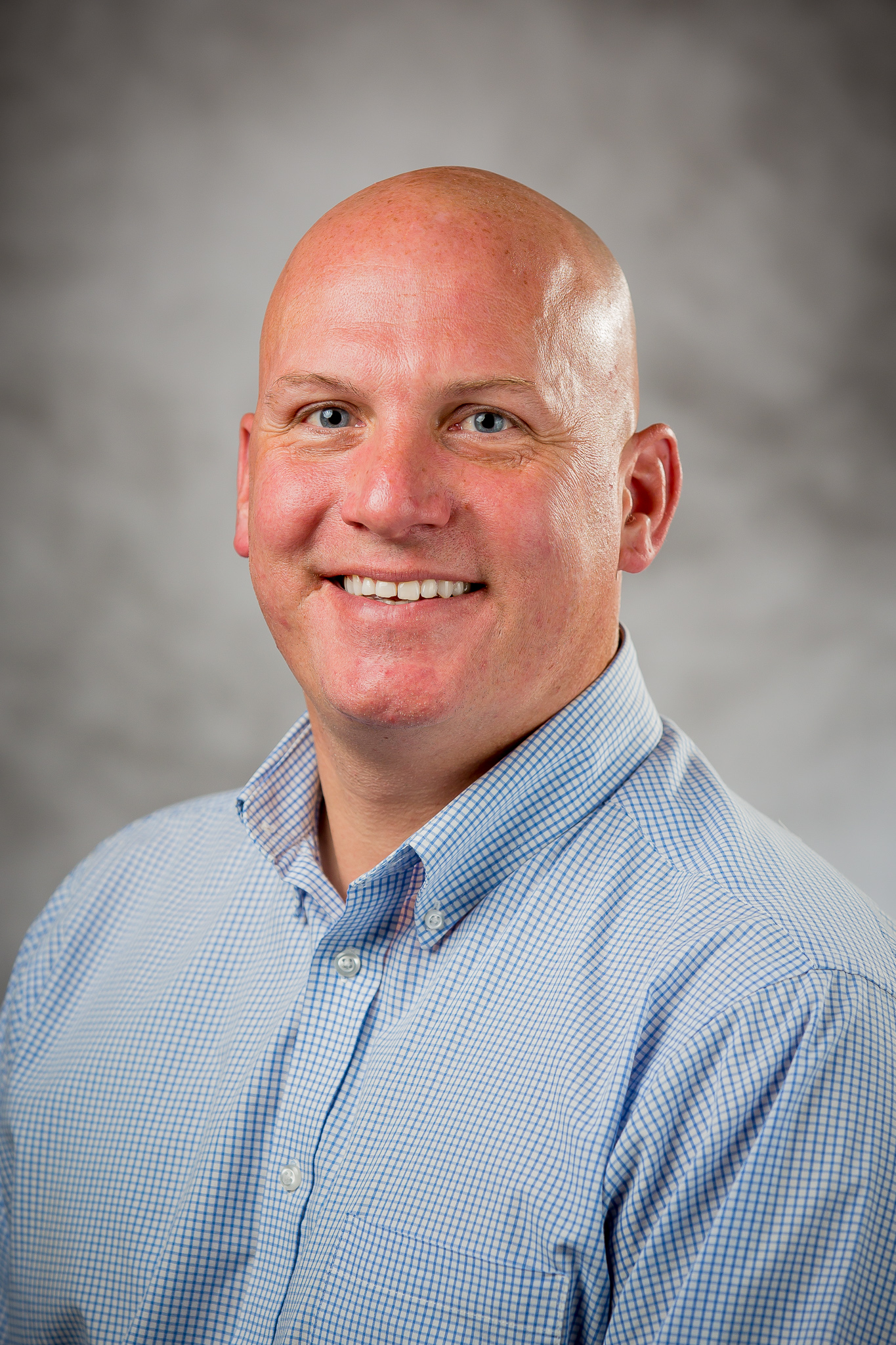 picture of a bald man wearing a blue button up shirt