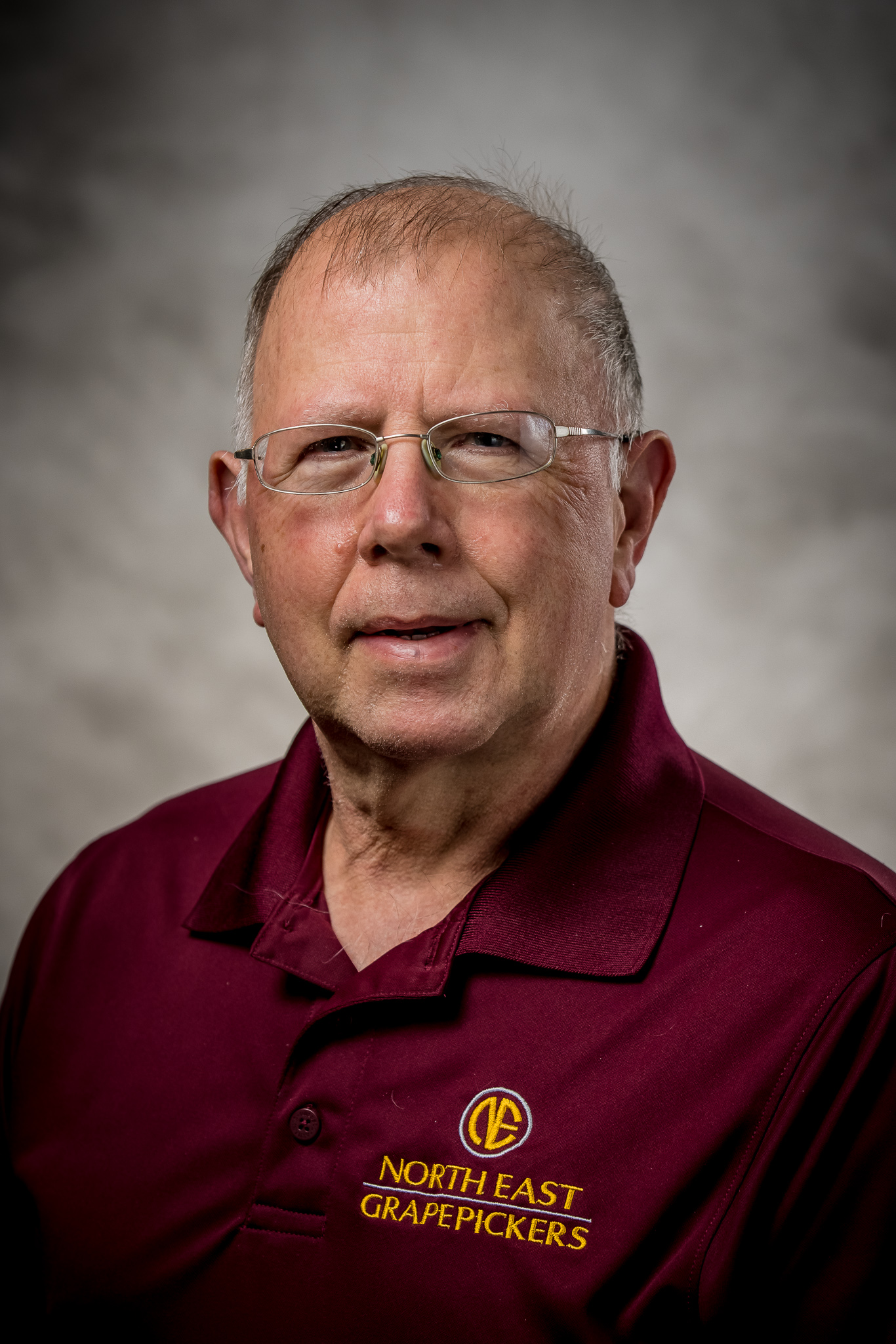 man wearing glasses and maroon collared shirt