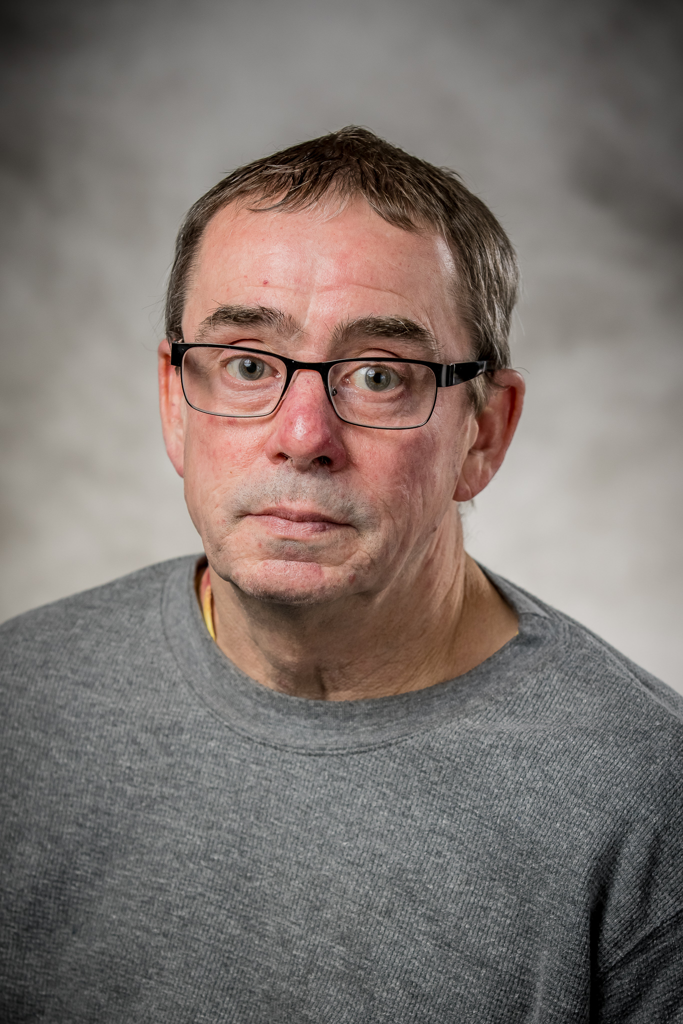 Man wearing glasses and grey crewneck
